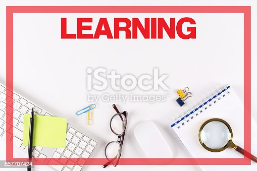 850892616istockphoto High Angle View of Various Office Supplies on Desk with a word LEARNING 857707424
