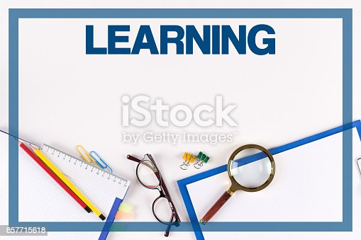 850892616 istock photo High Angle View of Various Office Supplies on Desk with a word LEARNING 857715618