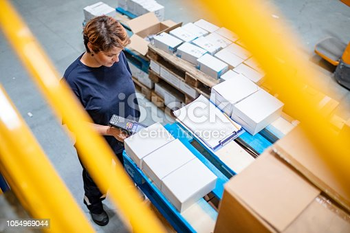 High angle view of warehouse employee using bar code reader for scanning information from boxes at warehouse
