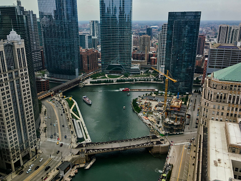 High angle view of Wolf Point on the Chicago River as a barge with debris heads north and tourist boat heads east.