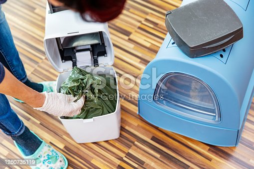 High Angle View of Woman Removing Full Garbage Bag from Cat Litter Disposal System