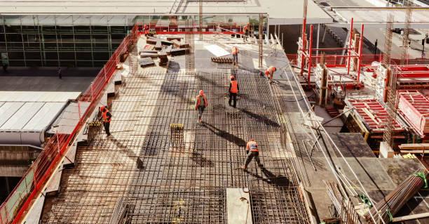 visione ad alto angolo dei lavoratori in cantiere - costruire foto e immagini stock