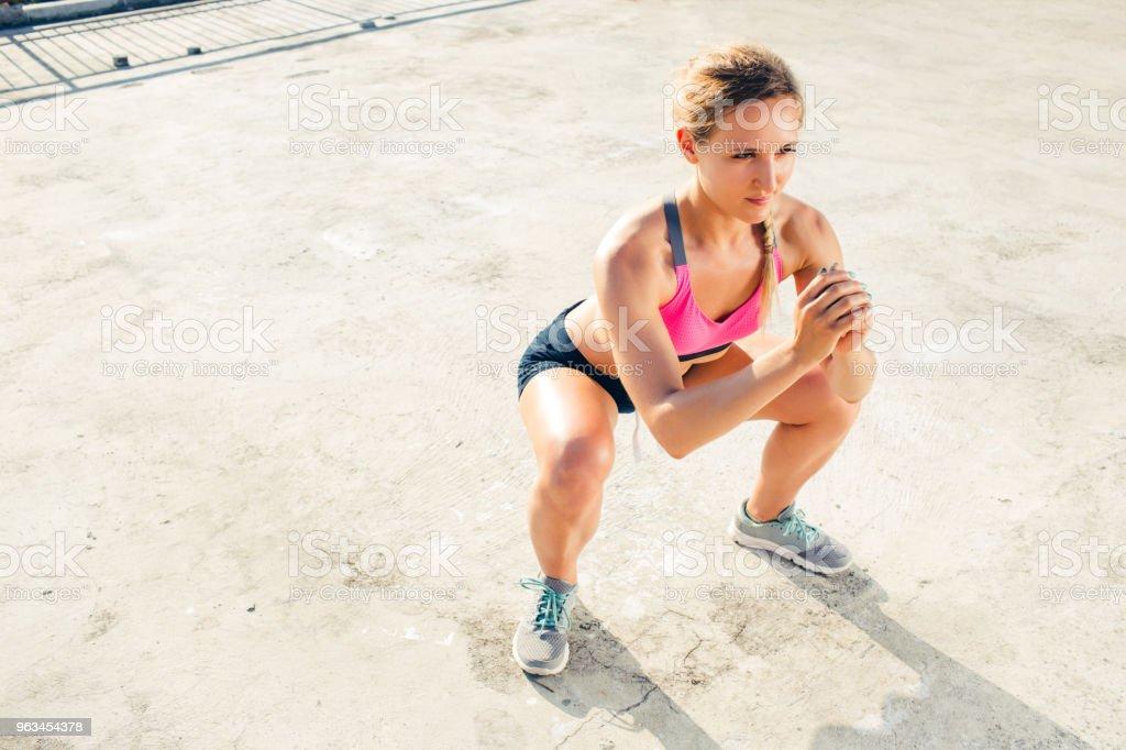 vue d'angle élevé de jeune sportive, faire de l'exercice de squat sur le toit - Photo de Accroupi libre de droits