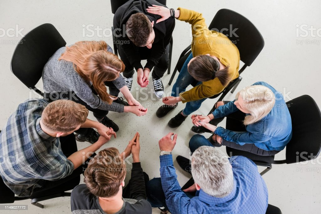 High angle view of young students and therapist High angle view of university students and therapist sitting during meeting. Mental health professional is with young men and women. They are in group therapy at lecture hall. 18-19 Years Stock Photo