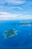 View from airplane on Borneo island and turquoise sea and sky.
