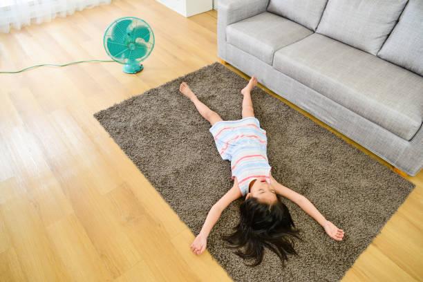 high angle view photo of girl lying down on carpet stock photo