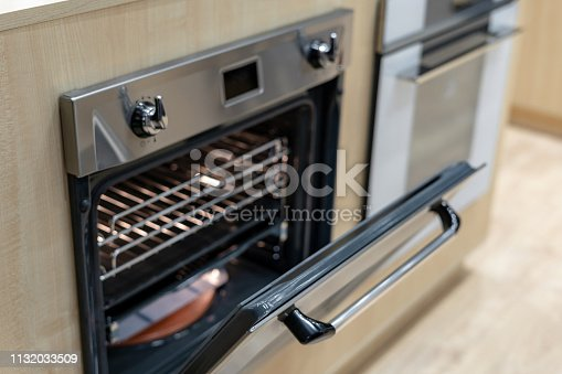 High angle view photo of open door on new and modern built-in oven in light bright kitchen