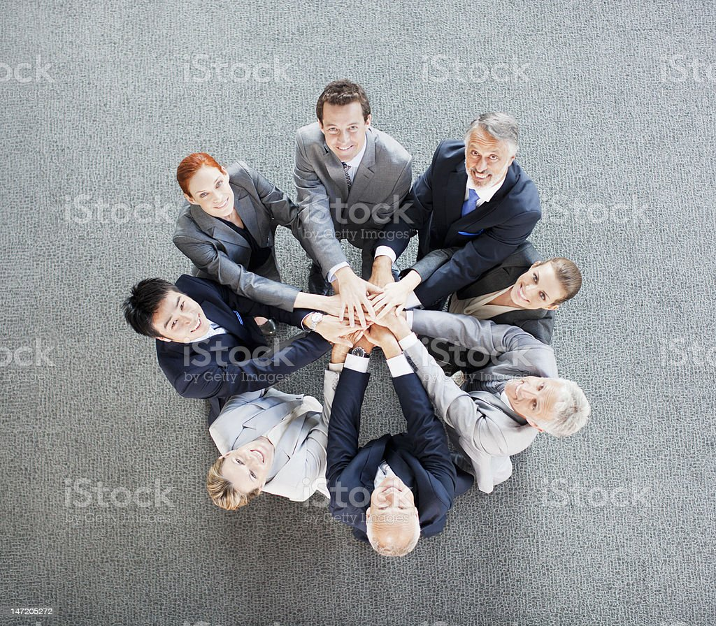 High angle view portrait of business people joining hands in circle stock photo