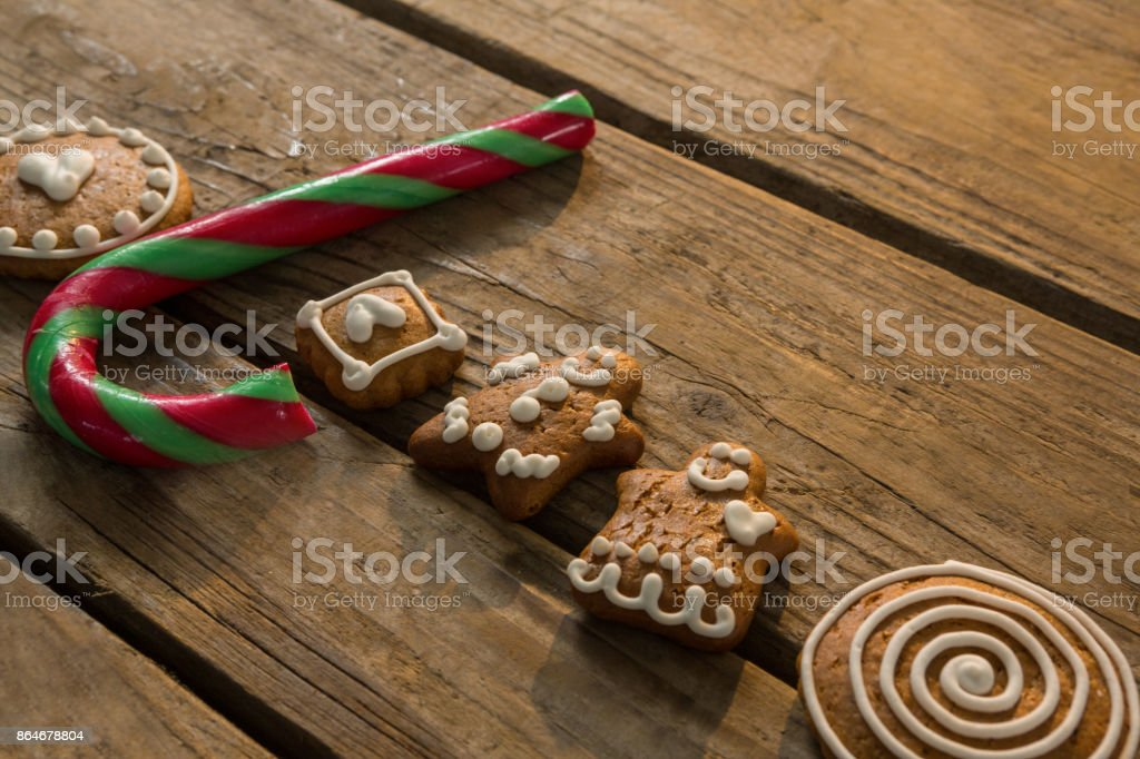 High angle view view of candy cane with gingerbread cookies arranged on table stock photo