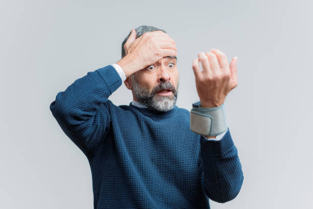 High blood pressure, worrying elderly man Senior man shocked with his blood pressure result, studio image hypertensive stock pictures, royalty-free photos & images