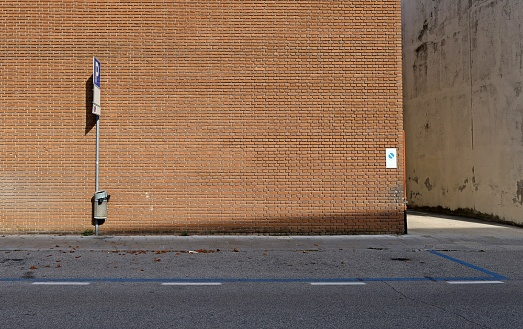 High brick wall, with sidewalk, street signs and asphalt road in front. Narrow street on the right. Background for copy space.