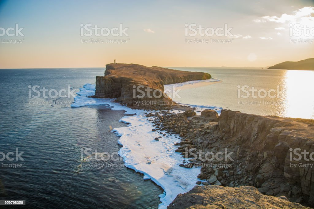 High cliffs into the sea, all in ice. Crag at sunset in the ice. a beautiful landscape from the outgoing Sun. stock photo