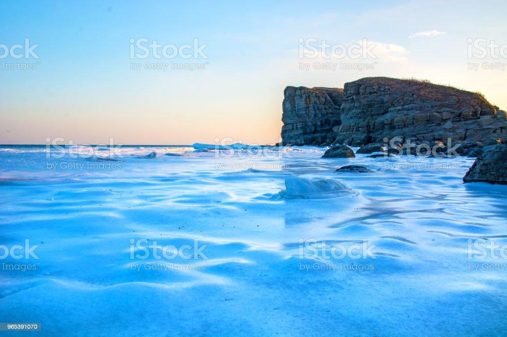 高高的懸崖進入大海, 全都在冰上。峭壁在冰的日落。一個美麗的風景從即將傳出的太陽。 - 免版稅俄羅斯圖庫照片
