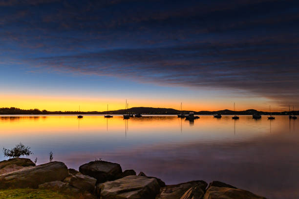 High Clouds, Boats, Reflections and Dawn on the Bay stock photo