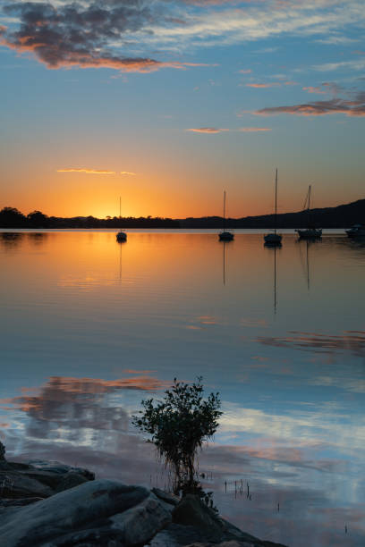 High Clouds, Boats, Reflections and Sunrise on the Bay stock photo