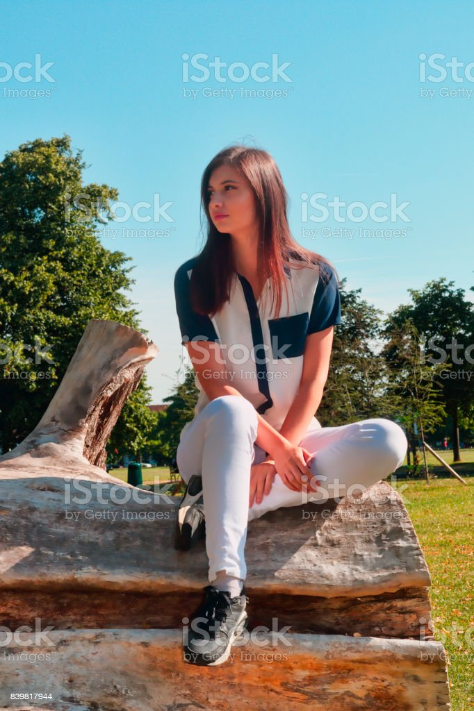 High colour serene Bulgarian outdoor girl smiling seated on log stock photo