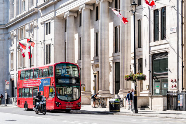 High Commission of Canada with red Canadian flags and double decker bus for Waterloo sign on Cockspur Street in Westminster stock photo