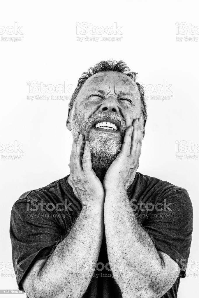 High contrast black and white portrait of a man with beard in pain closing his eyes. stock photo