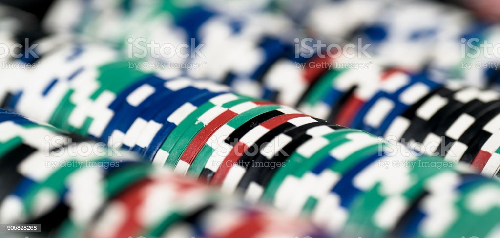 High contrast image of casino roulette and poker chips on bokeh background. stock photo