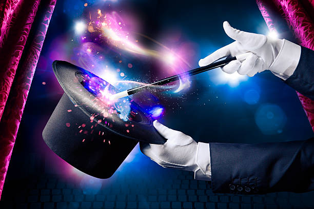 High contrast image of magician hand with magic wand Magician hand with magic wand and hat magic trick stock pictures, royalty-free photos & images