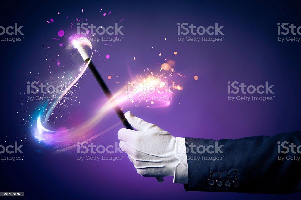 High contrast image of magician hand with magic wand stock photo