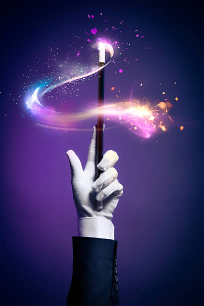 High contrast image of magician hand with magic wand Magician hand with magic wand magician stock pictures, royalty-free photos & images