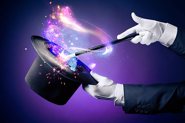 High contrast image of magician hand with magic wand Magician hand with magic wand and hat magician stock pictures, royalty-free photos & images