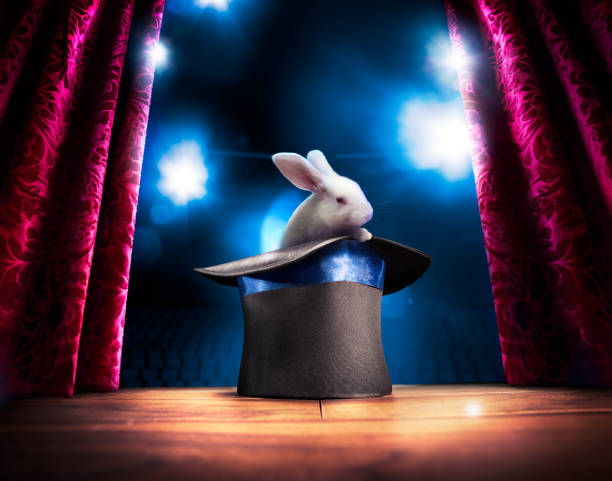 High contrast image of magician hat on a stage photo composite of a bunny in a magic hat on a stage magician stock pictures, royalty-free photos & images