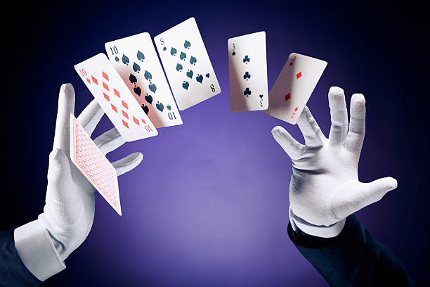 High contrast image of magician making card tricks Magician hands with magic cards magic trick stock pictures, royalty-free photos & images