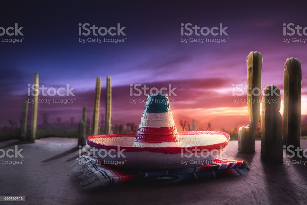 high contrast image of Mexican hat 'sombrero' on a 'serape' in a desert at twilight stock photo