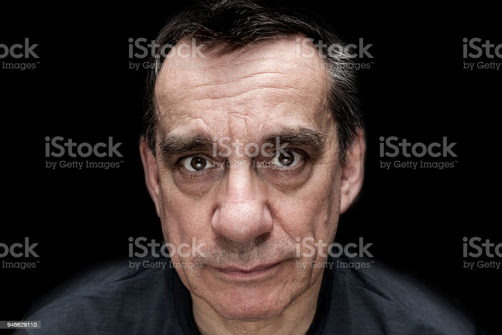 High contrast portrait of sad unhappy looking man stock photo