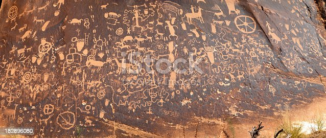 Ancient Anasazi rock petroglyphs carved into the edge of a rock face in Canyonlands National Park, Utah. High detail panoramic which captures nearly all of the etchings into the sandstone.