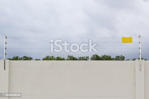 high electric fence with blank yellow sign on concrete wall, security fence for house in cloudy day.