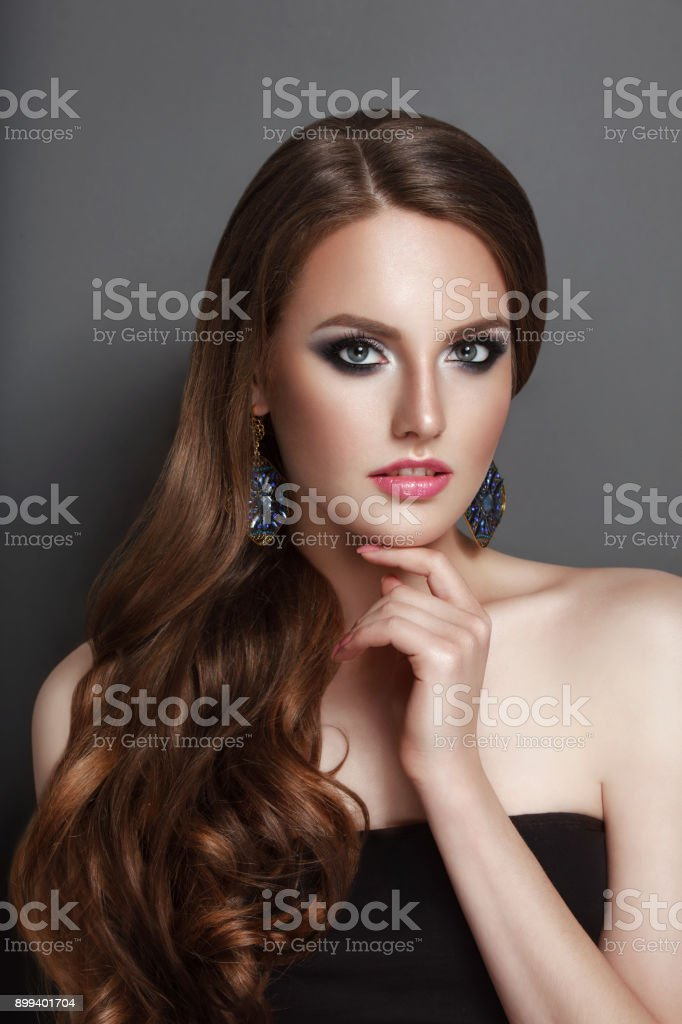 High Fashion Beauty Model Girl en face view with long curly curve brunette hair black corset and huge earings stock photo