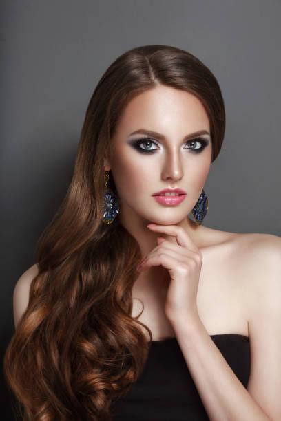 high fashion beauty model mädchen de flächenansicht mit langen lockigen kurve brünette haare schwarzes korsett und große ohrringe - haarverlängerung stock-fotos und bilder