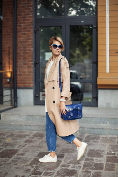 High Fashion Clothing. Beautiful Sexy Woman Wearing Fashionable Spring Or Fall Clothes (beige trench coat, blue bag, jeans, accessories, sunglasses) Outdoors. Female Model In Stylish Elegant Outfit walking Street. Autumn trend 2018. stock photo