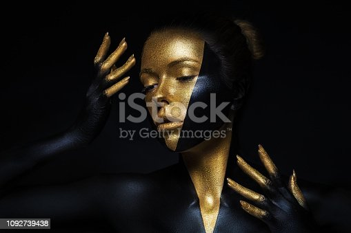 High fashion model with black and gold leather, golden fingers. Isolated on black background Beauty female face, creative make-up.