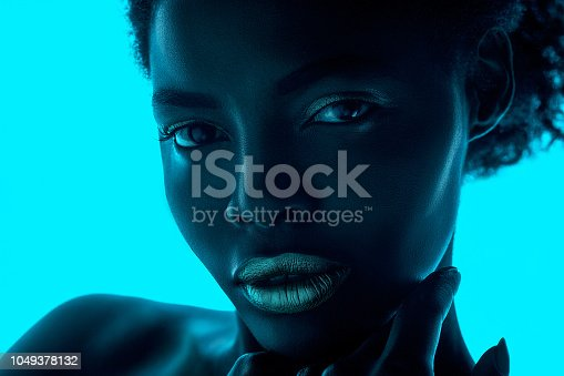 1049378188 istock photo High Fashion model woman in colorful bright lights posing in studio 1049378132