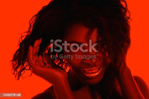 1049378188 istock photo High Fashion model woman in colorful bright lights posing in studio 1049378148