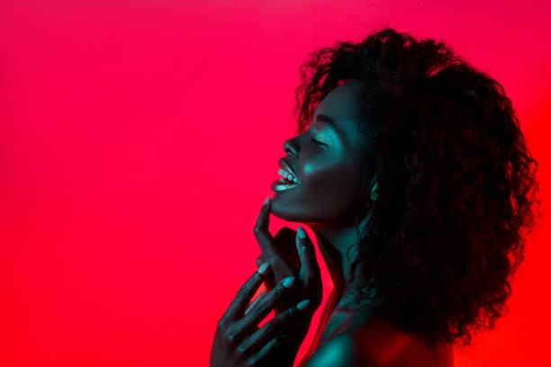 mujer de modelo de alta moda en colores brillantes luces posando en el estudio - moda de maquillaje fotografías e imágenes de stock