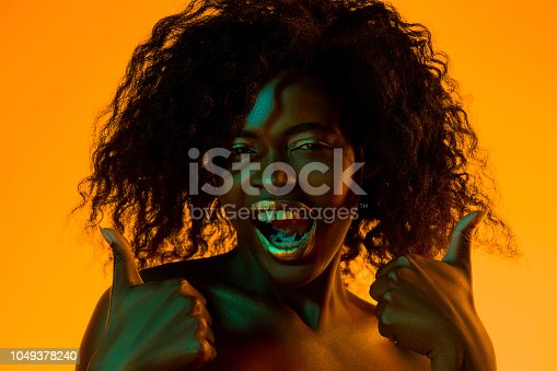 1049378188 istock photo High Fashion model woman in colorful bright lights posing in studio 1049378240