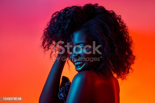 High Fashion model woman in colorful bright lights posing in studio, portrait of african girl with trendy make-up. Art design, colorful make up. Over colourful vivid background.
