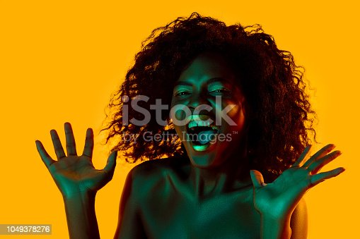 1049378188 istock photo High Fashion model woman in colorful bright lights posing in studio 1049378276