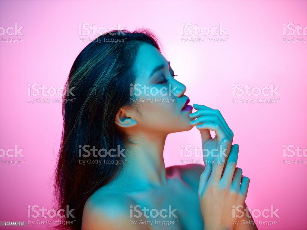 High Fashion model woman in colorful bright lights posing in studio, portrait of african girl with trendy make-up. - Zbiór zdjęć royalty-free (Abstrakcja)