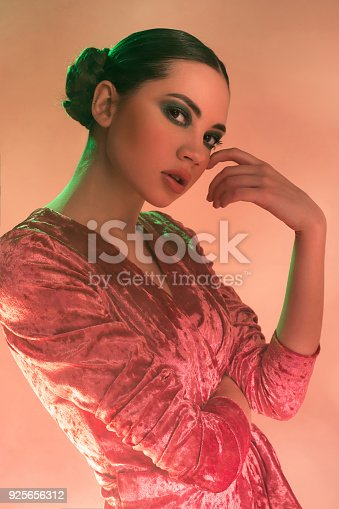 926617828istockphoto High Fashion model woman in colorful bright lights posing in studio 925656312