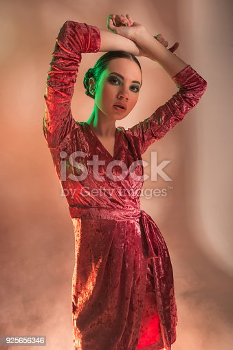 926617828istockphoto High Fashion model woman in colorful bright lights posing in studio 925656346