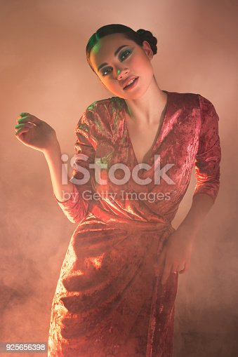 926617828istockphoto High Fashion model woman in colorful bright lights posing in studio 925656398