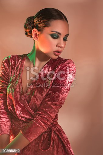926617828istockphoto High Fashion model woman in colorful bright lights posing in studio 925656540