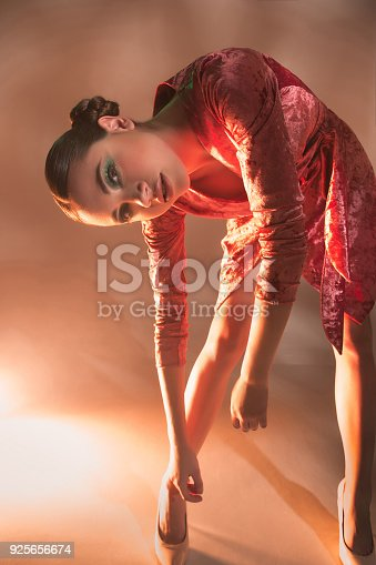 926617828istockphoto High Fashion model woman in colorful bright lights posing in studio 925656674
