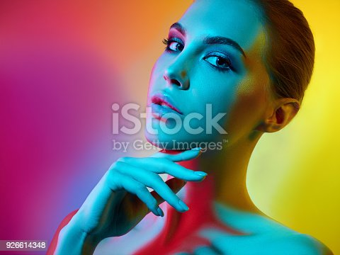 926617828istockphoto High Fashion model woman in colorful bright lights posing in studio 926614348
